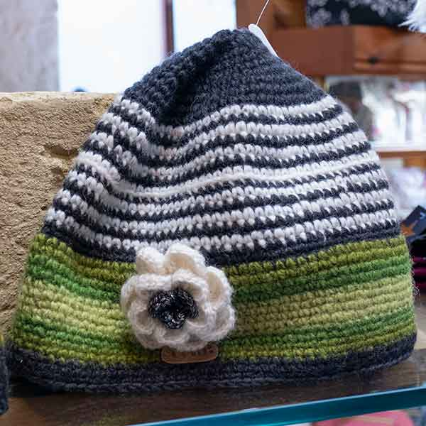 green and white stripy knitted hat with flower