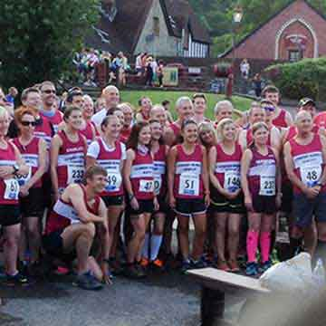 runners in red vests at race event highlight