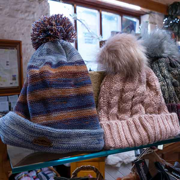mauve and rust stripy and pale pink cable knit fluffy pom pom bobble hats