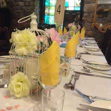 wedding function table setting with yellow and pink serviettes and flowers