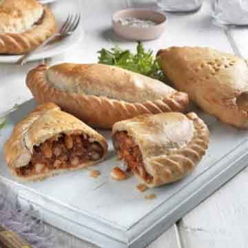 whole and cut cornish pasties on white wood surface