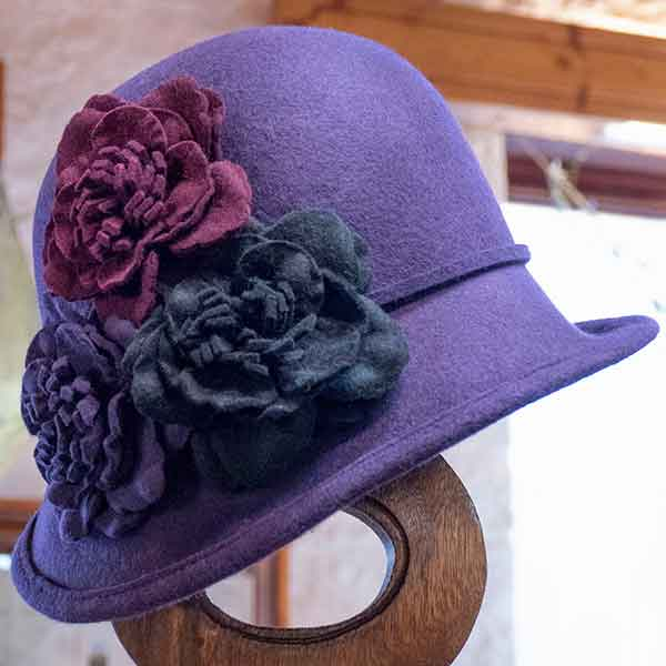 purple felt cloche hat with three contrasting flowers view