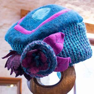 Turquoise and mauve contrast knitted hat with chunky flowers