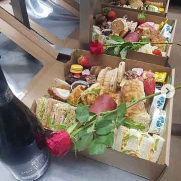 three open afternoon tea boxes with red rose and prosecco wine