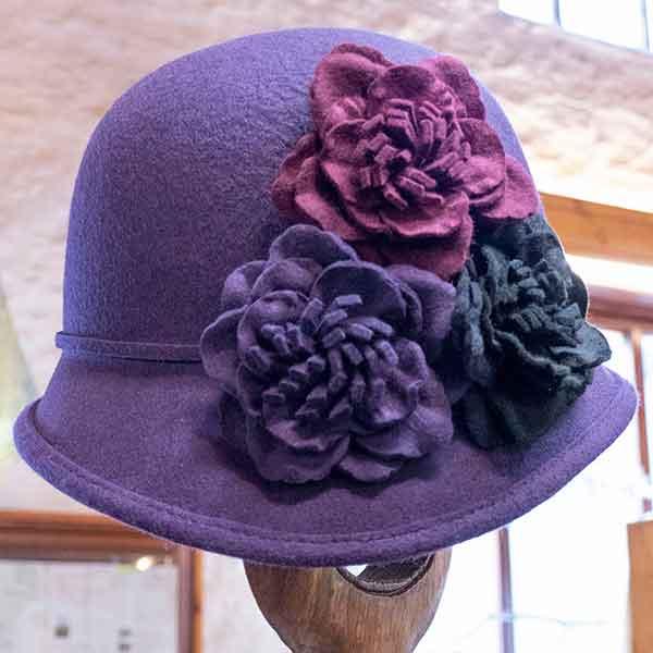 purple felt cloche hat with three contrasting flowers