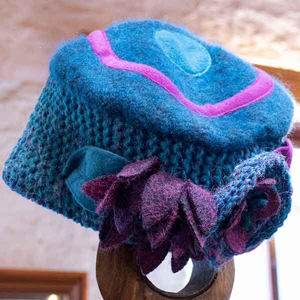 turquoise and mauve contrast knitted hat with chunky flowers view