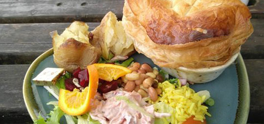 Woodsaw & Wheel puff pastry meat pie and jacket potato with salad, beans, rice and coleslaw
