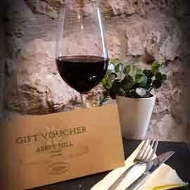 Abbey Mill gift voucher on a table setting with glass of red wine